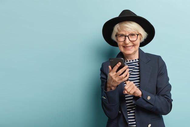 Mulher feliz idosa tem óculos ópticos, faz transações bancárias on-line no celular, usa tecnologias modernas para pesquisar informações na internet, veste roupas da moda, sorri amigável, isolada