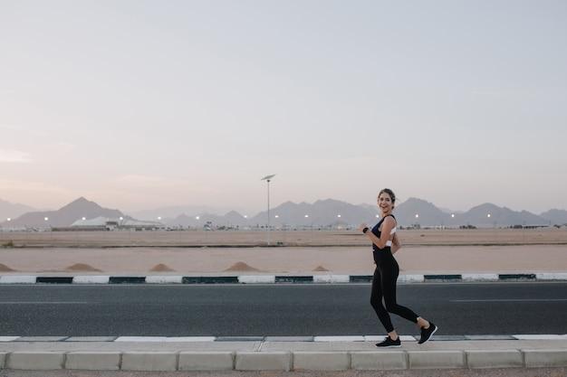 Mulher feliz incrível alegre animada correndo na estrada do país tropical. sorrir, expressar positividade, emoções verdadeiras, estilo de vida saudável, treino ...