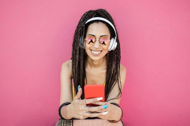 Mulher feliz influenciadora boêmia ouvindo música de lista de reprodução com fundo rosa - foco no rosto