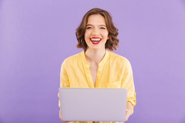 Mulher feliz isolada sobre o uso de computador portátil