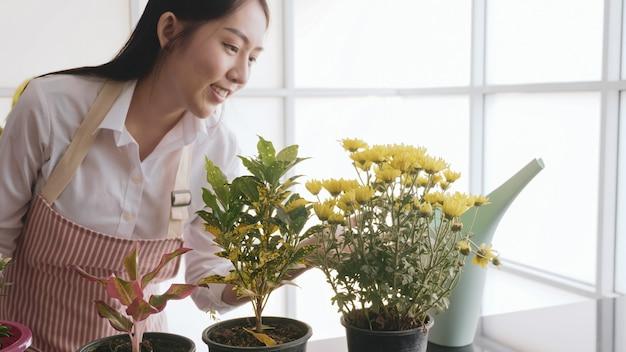 Mulher feliz jardineiro olhando flores em vaso.