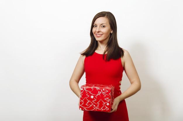 Mulher feliz jovem caucasiana bonita com sorriso encantador vestida com um vestido vermelho e chapéu de natal segurando uma caixa de presente em fundo branco. menina santa com presente isolado. conceito de feriado de ano novo 2018