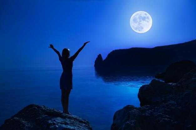 Mulher feliz jovem não identificada de vista traseira fica em um levantamento de pedra mãos para cima olhando para a lua grande e a água do mar clara calma contra o pano de fundo da paisagem e do céu noturno claro. conceito de lua cheia