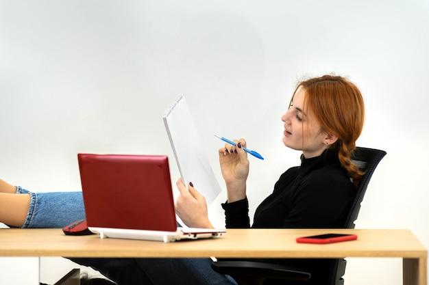 Mulher feliz jovem trabalhador de escritório sentado relaxado com os pés na mesa atrás da mesa de trabalho com o computador portátil, o telefone celular e o notebook.