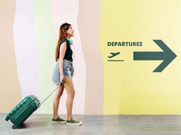 Mulher feliz jovem viajante andando com mala no aeroporto de partidas