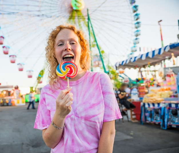 Mulher feliz lambendo um pirulito no parque de diversões
