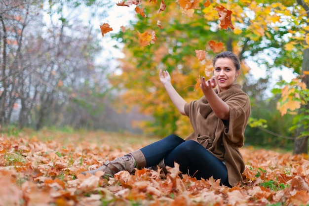 Mulher feliz lança folhas de outono