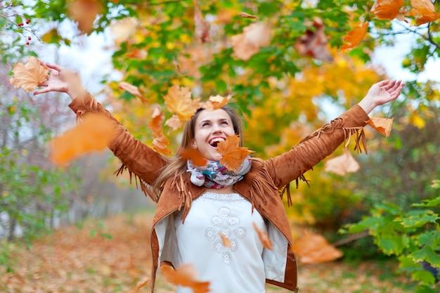 Mulher feliz lança folhas