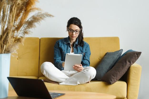 Mulher feliz lendo um livro em um leitor de e-book, sentada em um sofá em casa