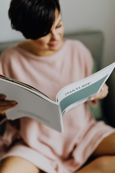 Mulher feliz lendo uma revista