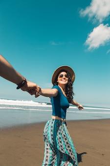 Mulher feliz levando o homem através da areia da praia
