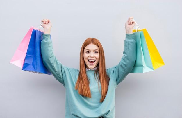 Mulher feliz levantando sacos de papel
