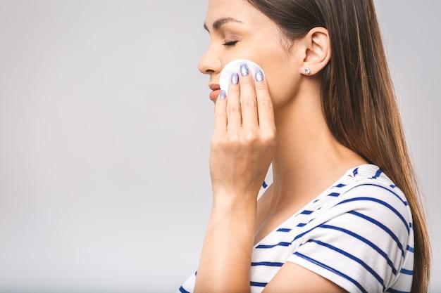 Mulher feliz limpando o rosto com almofadas de algodão