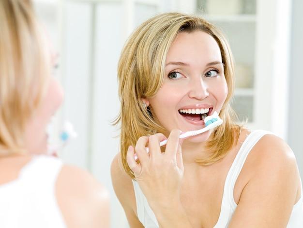 Mulher feliz limpando os dentes com escova de dentes