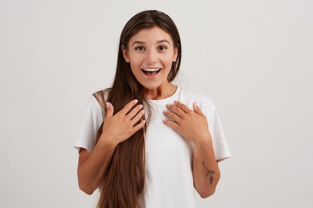 Mulher feliz, linda garota com cabelo comprido escuro, vestindo camiseta branca e tem tatuagem