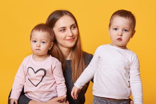 Mulher feliz, mãe e suas crianças gêmeas posa no estúdio de fotografia