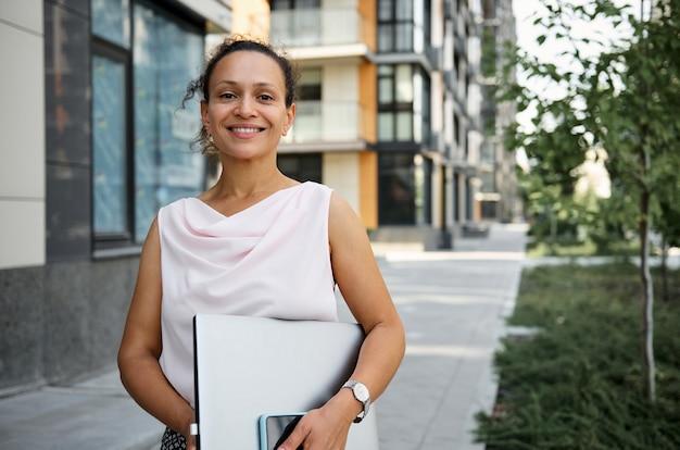 Mulher feliz morena de raça mista em traje casual, segurando o computador portátil, sorrindo, olhando para a câmera no fundo de edifícios altos. negócios, freelance, conceito de trabalho de escritório
