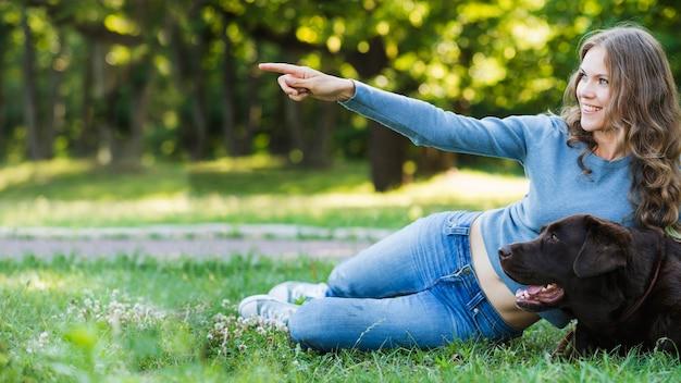 Mulher feliz, mostrando, algo, para, dela, cão, parque