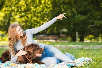 Mulher feliz mostrando algo para seu cachorro no jardim