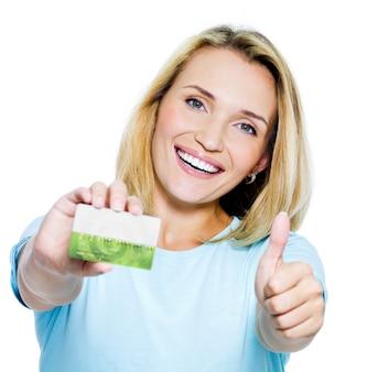 Mulher feliz mostrando o polegar para cima com cartão de crédito