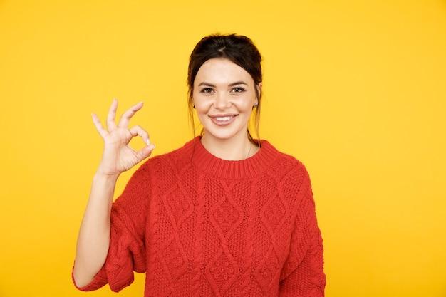 Mulher feliz mostrando ok isolado na parede amarela brilhante.