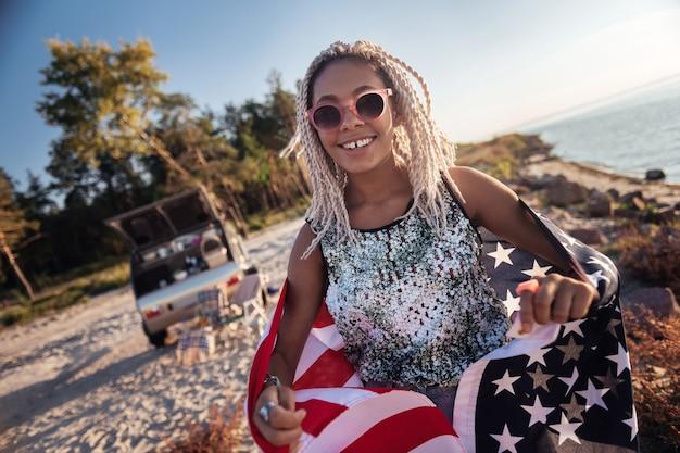Mulher feliz. mulher atraente e feliz com dreadlocks se sentindo alegre viajando com um trailer compacto