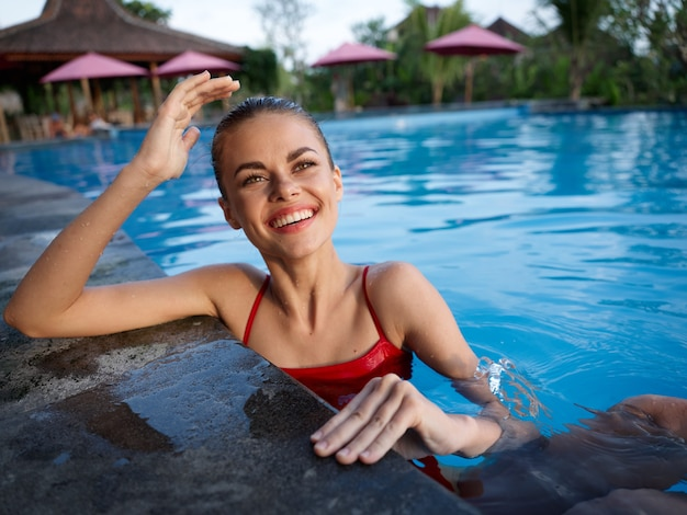 Mulher feliz na água da piscina transparente sorriso modelo emoção risada
