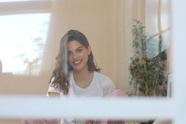Mulher feliz na cama, sorrindo e se espreguiçando, olhando para a câmera.