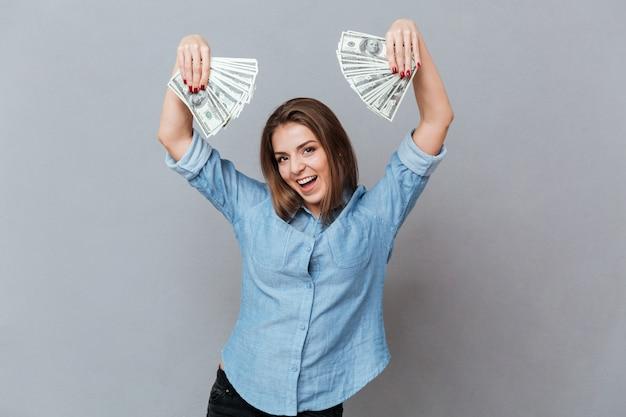 Mulher feliz na camisa com dinheiro nas mãos
