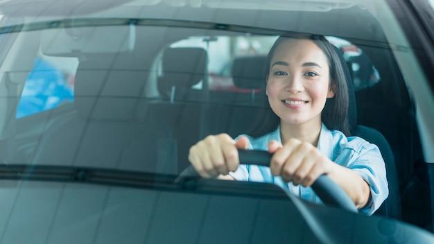 Mulher feliz na concessionária de carros