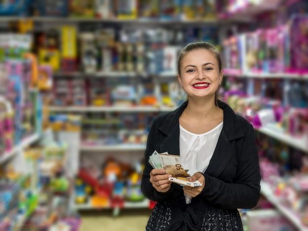 Mulher feliz na loja de brinquedos segurando notas de euro