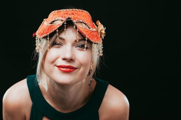 Mulher feliz na máscara de carnaval laranja