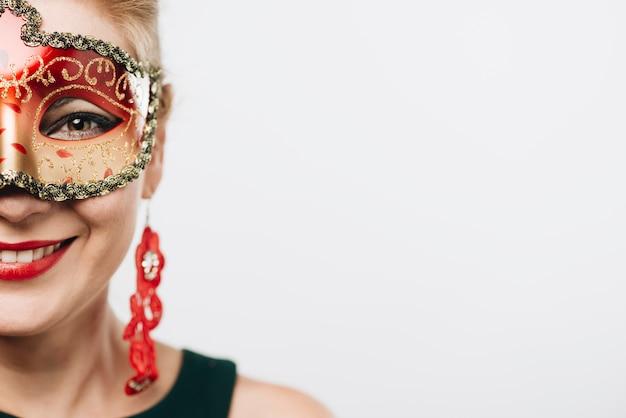 Mulher feliz na máscara de carnaval vermelho brilhante