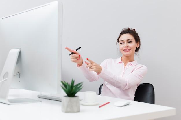 Mulher feliz na mesa apontando para o computador