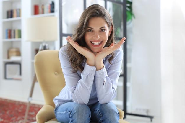 Mulher feliz na poltrona, sorrindo e se esticando, olhando para a câmera.