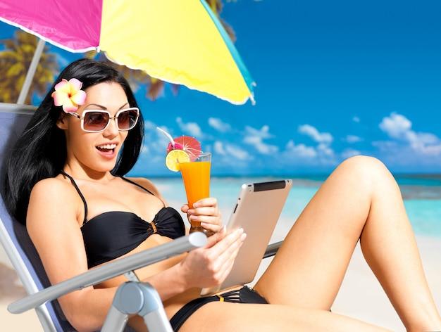 Mulher feliz na praia com ipad.
