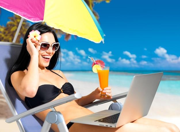 Mulher feliz na praia com um laptop.