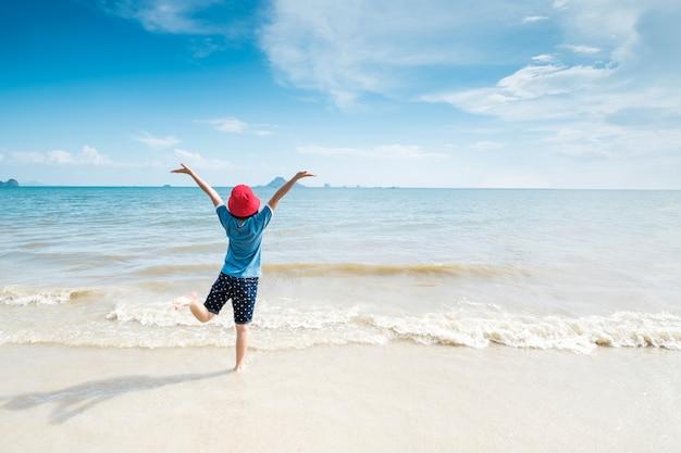 Mulher feliz na praia e céu das nuvens.