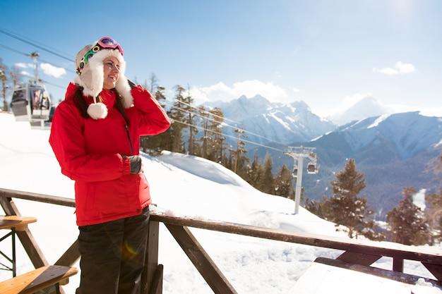 Mulher feliz nas montanhas nevadas. férias de esporte de inverno.