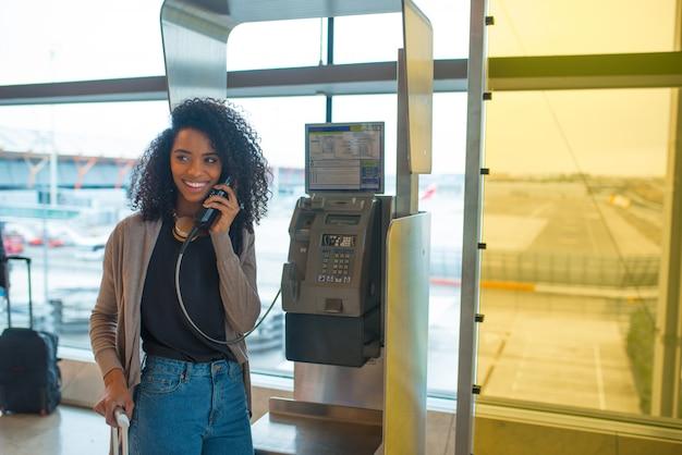Mulher feliz no aeroporto falando por telefone público