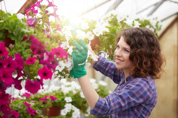 Mulher feliz no berçário aparando plantas na estufa