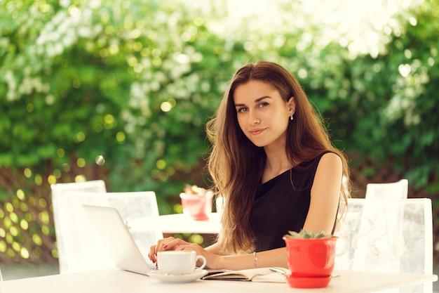 Mulher feliz no café ao ar livre