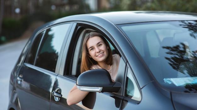 Mulher feliz no carro com tiro médio