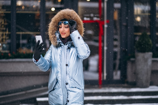 Mulher feliz no casaco azul falando ao telefone