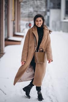 Mulher feliz no casaco no inverno lá fora