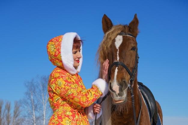 Mulher feliz no inverno com um cavalo na rua