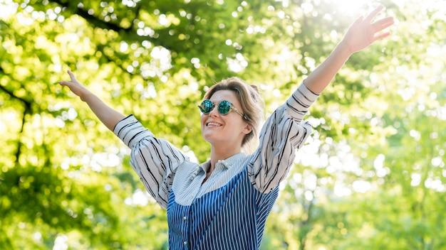 Mulher feliz no parque de verão tiro médio