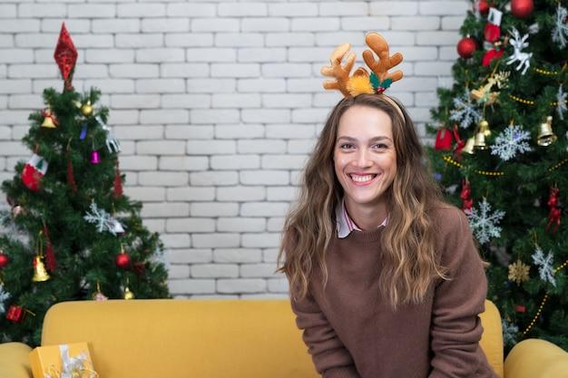 Mulher feliz no sofá. árvore de natal com presentes embaixo. sala decorada
