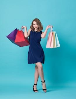 Mulher feliz no vestido azul e mão que mantém o saco de compras isolado sobre o azul.