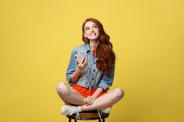 Mulher feliz nos fones de ouvido que escuta a música e que canta ao sentar e ao guardar o telefone celular.